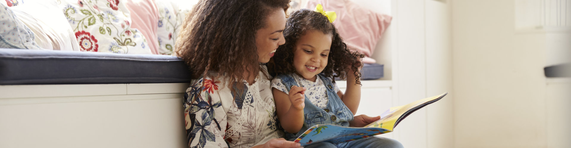 woman reading to a little girl